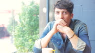 Portrait of a young man sitting in the coffee shop. video