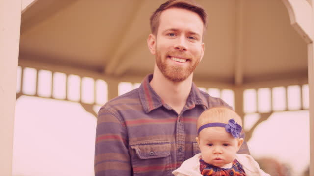 Portrait of a young man sitting with his baby daughter under a gazebo on a fall day video