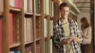 DS Portrait of young man by library bookshelf with tablet video