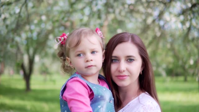 Portrait of a young mother and little daughter in the park video