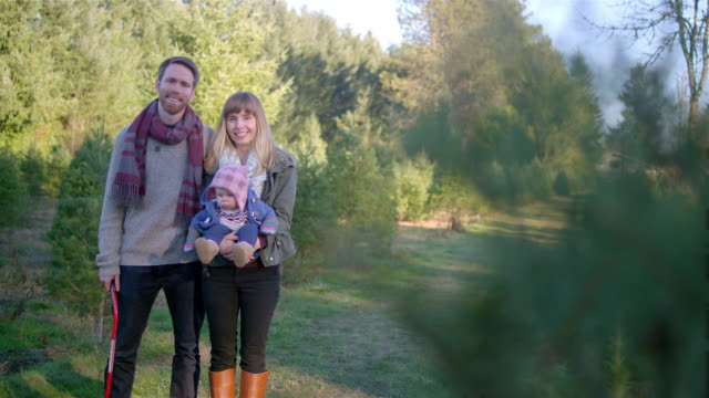 Portrait of a young mother, father and their baby girl at a Christmas tree farm, parents kiss video