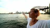 Portrait of a young woman arms outstretched at Sydney harbour video