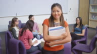 Portrait of a young woman holding her homework and standing in front of her classmates video