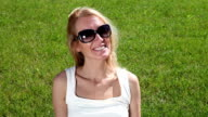 Portrait of a young woman on a green lawn video