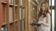 TU Portrait of young woman thumbing through a book video