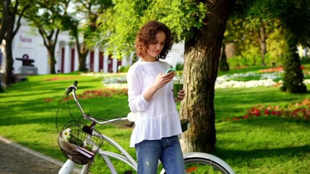 Portrait of a young woman typing a message using her smartphone standing in the city park near her city bicycle with flowers in its basket and drinking green detox smoothie. Healthy lifestyle video