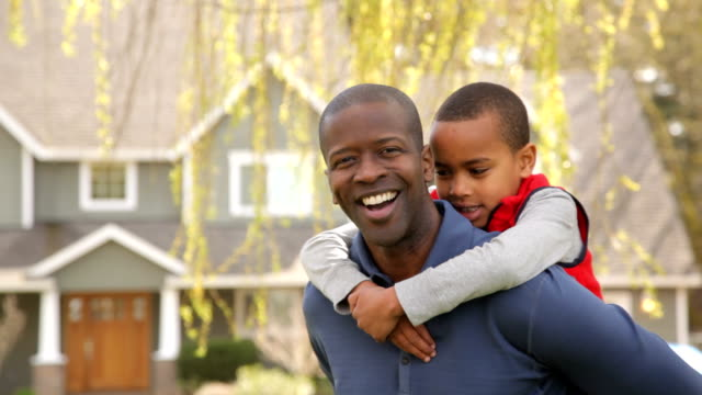 Portrait of African American father and son outdoors in yard video