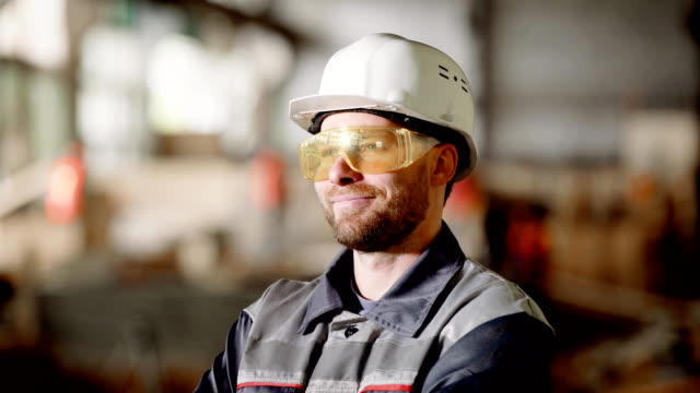 Portrait of an adult construction worker in a protective helmet, a person enjoys the process of building high-quality construction of his subordinates video