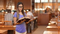 DS Portrait of Asian student leafing through book in library video
