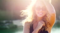 Portrait of an attractive young woman smiling at the camera in the sun against the sea. The wind and the sun playing with her hair video