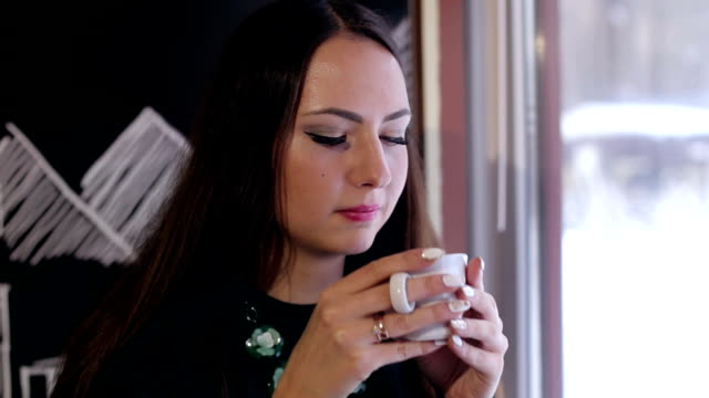 Portrait of attractive girl with a cup of coffee. video