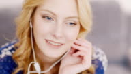 Portrait of attractive young caucasian woman who listens to music on headphones video