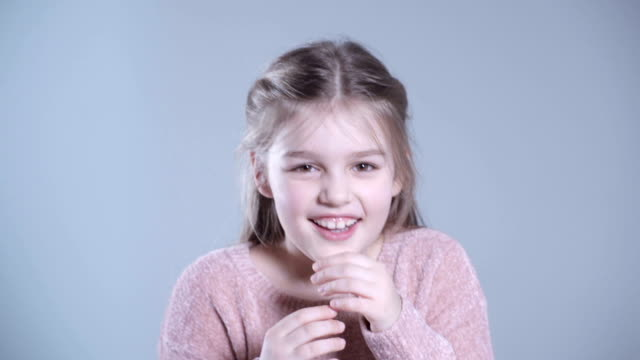 Portrait of beautiful child girl model with long hair laughing in studio. video