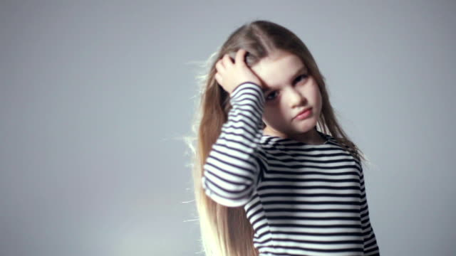 Portrait of beautiful child girl model with long hair looking at camera. video