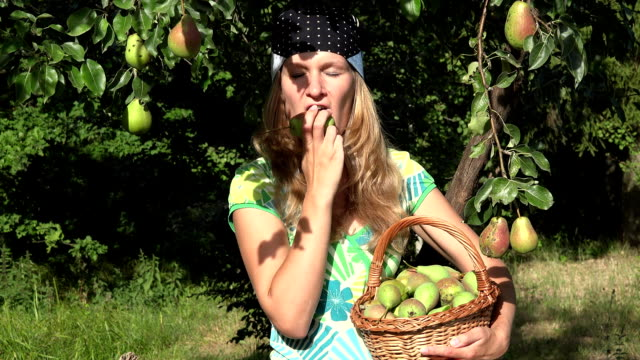 Portrait of beautiful happy gardener woman holding basket of fruit and eating ripe pears. FullHD video