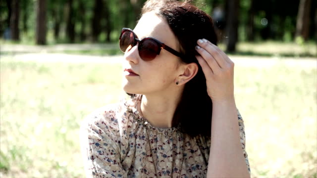 Portrait of beautiful young girl sitting on grass in sunglasses video