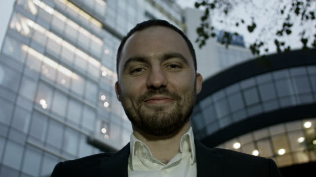 Portrait of business man joking and showing the tongue against a office building video