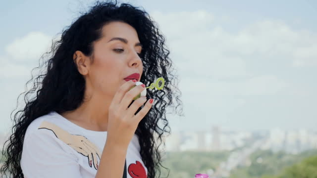 Portrait of charming curly girl blows bubbles video