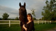 SLOW MOTION: Portrait of cheerful girl petting and kissing tall dark bay horse video