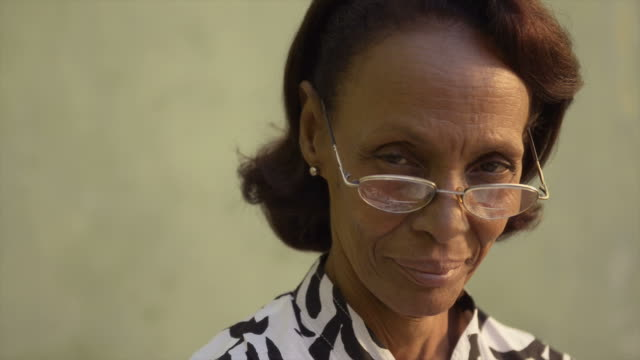 Portrait of confident old black lady with eyeglasses smiling video