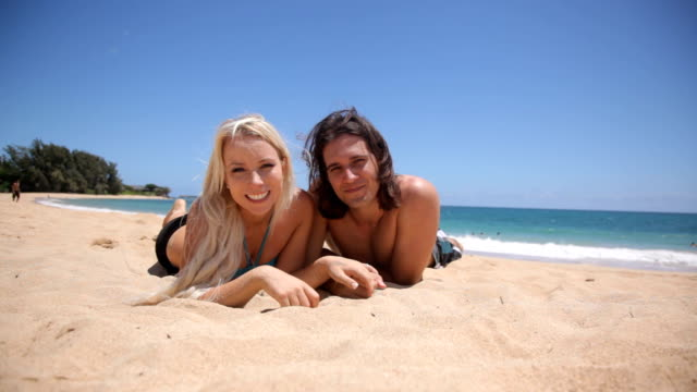Portrait of couple laying in sand at tropical beach video