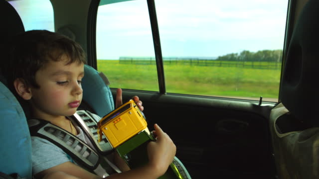 Portrait of cute boy with a toy in car video