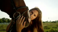 CLOSE UP: Portrait of cute brunette girl kissing and petting cute horse's muzzle video