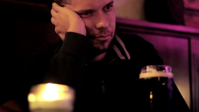 Portrait of depressed young men drinking beer at the pub video