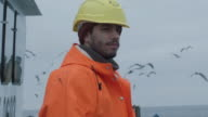 Portrait of Dressed in Bright Protective Coat Smiling Fisherman on Commercial Fishing Boat. video