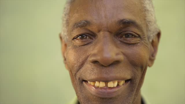 Portrait of elderly black man looking and smiling at camera video