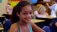 Portrait of elementary school girl in classroom video