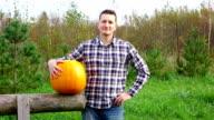 Portrait of Farmer with big orange pumpkin, good harvest video