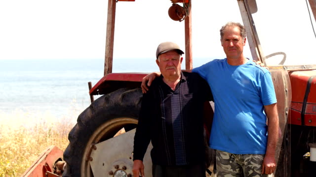 Portrait of farmers in front of a tractor, they are tired after harvesting video