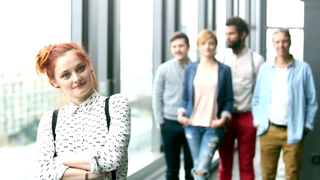 Portrait of female advertising executive, colleagues in background video
