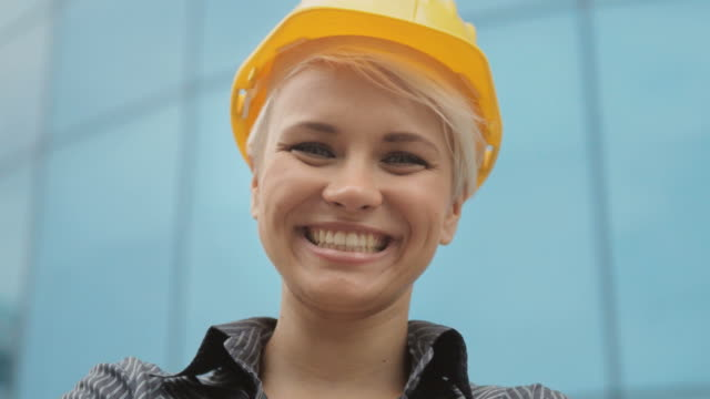 Portrait of female engineer with helmet smiling at camera video