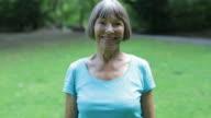 Portrait of fit senior woman smiling at park video