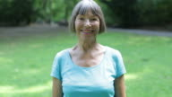 Portrait of fit senior woman smiling in park video