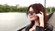 Portrait of girl in sunglasses on bridge of river. video