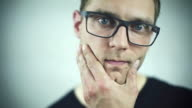 Portrait of handsome caucasian man in glasses wondering and looking at camera. video
