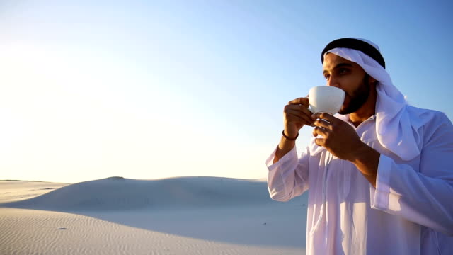 Portrait of handsome young Arabian Sheikh who drinks from cup of coffee, standing in middle of desert against blue sky in open air video