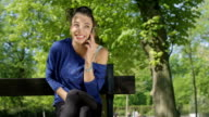 A portrait of happy beautiful woman talking on her phone in sunny park. video