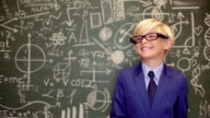 Portrait of happy boy lerning before blackboard with sums on it during lesson video