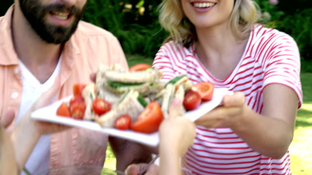Portrait of happy family is eating in the garden video