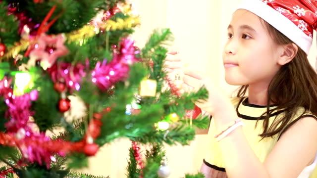 Portrait of happy girl decorating Christmas tree video