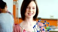 Portrait of happy schoolgirl experimenting molecule model in laboratory video