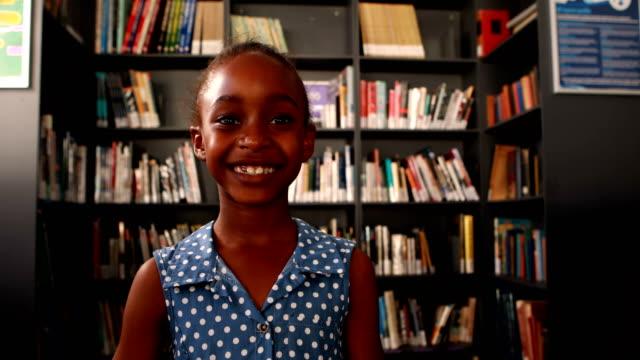 Portrait of happy schoolgirl standing in library 4k video