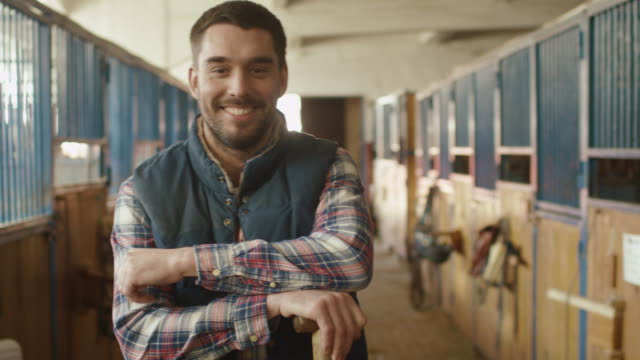 Portrait of happy smiling farmer with a pitchfork in a stable. video