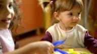 Portrait of happy teacher with children eating in kindergarten video
