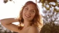SLO MO Portrait of happy woman swinging in sunshine video