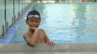 Portrait of little boy on swimming pool edge slowmotion video